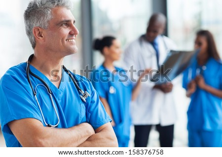 portrait of confident senior medical doctor in hospital - stock photo