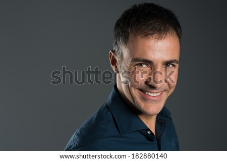 Portrait Of Confident Smiling Mature Man On Grey Background - stock photo