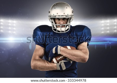 Portrait of confident sportsman holding ball against spotlights