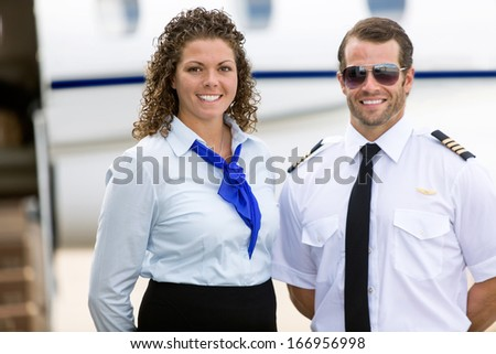 Portrait of confident stewardess and pilot standing against private jet - stock photo