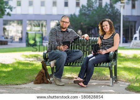 Portrait of confident students with digital tablets sitting together on bench at university campus - stock photo