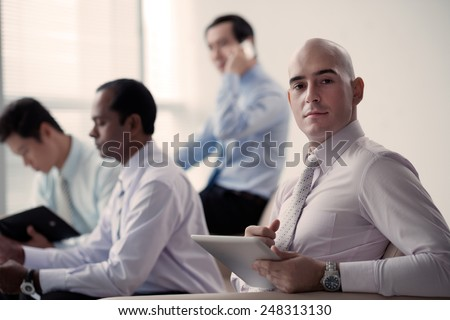 Portrait of confident successful businessman with a tablet computer - stock photo