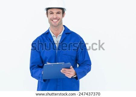 Portrait of confident supervisor writing notes over white background - stock photo