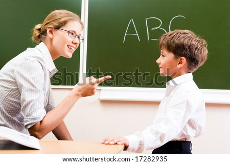 Portrait of confident teacher explaining grammar to schoolchild who looking at her attentively
