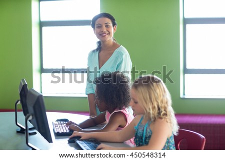 Portrait of confident teacher with children in computer class - stock photo