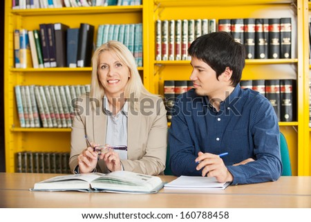Portrait of confident teacher with student looking at her in college library - stock photo