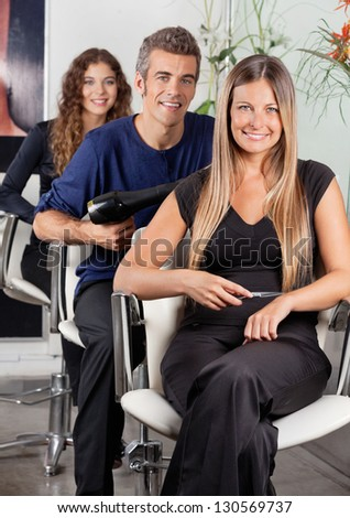 Portrait of confident team of hairdressers sitting at hair salon