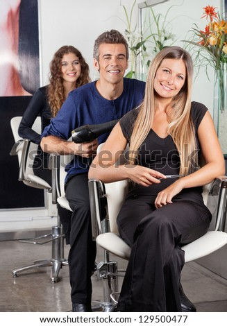 Portrait of confident team of hairstylists sitting at beauty parlor
