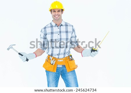 Portrait of confident technician holding hammer and measure tape over white background - stock photo