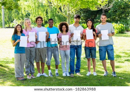 Portrait of confident university students holding blank papers on campus
