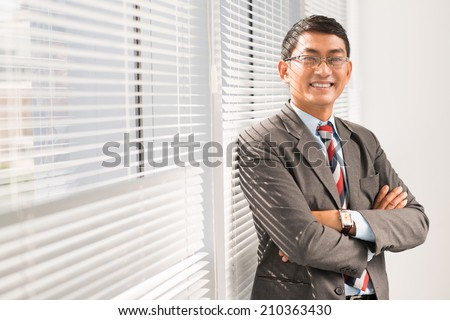 Portrait of confident Vietnamese businessman with his arms folded - stock photo