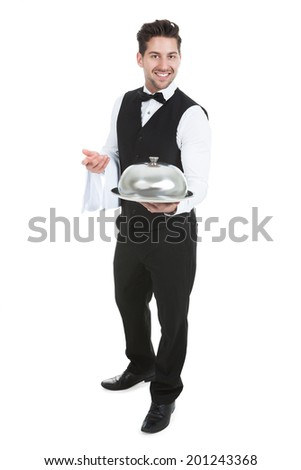 Portrait of confident waiter holding domed tray isolated over white background - stock photo
