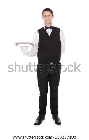 Portrait of confident waiter holding empty tray over white background - stock photo