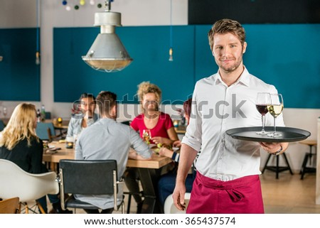 Portrait of confident waiter holding tray at restaurant with customers in background - stock photo