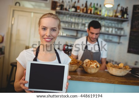 Portrait of confident waitress holding blank chalkboard with colleague at cafe - stock photo