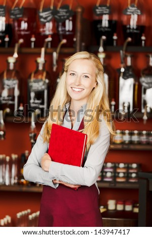 Portrait of confident waitress holding book in cafe