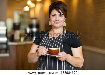 Portrait of confident waitress holding coffee cup while standing in cafe - stock photo