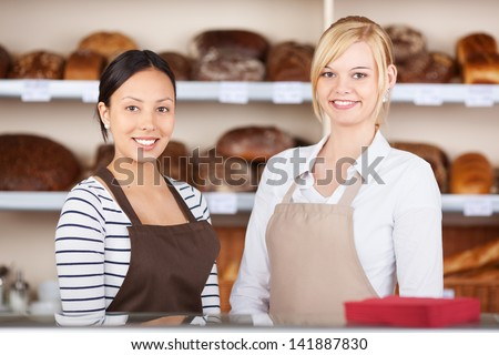 Portrait of confident waitresses standing together at cafe counter - stock photo
