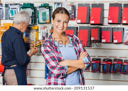 Portrait of confident woman with arms crossed standing against worker in hardware store