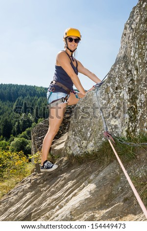 Portrait of confident woman with climbing equipment standing on rock