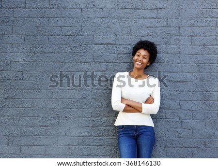 Portrait of confident young african woman standing against a gray wall  - stock photo