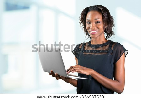 Portrait of confident young african woman using laptop
