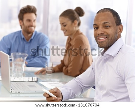 Portrait of confident young afro businessman sitting at a meeting, using mobilephone. - stock photo