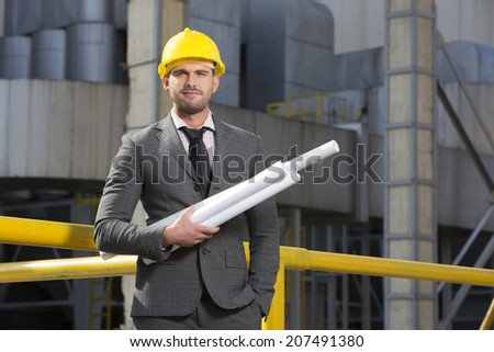 Portrait of confident young architect holding blueprints outside industry - stock photo
