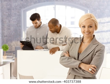Portrait of confident young attractive businesswoman, smiling, looking at camera. - stock photo