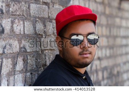 Portrait of confident young black boy in red baseball cap at grey brick wall  with graffiti on the background - stock photo