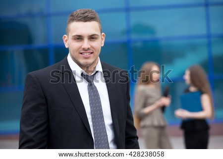 Portrait of confident young business man looking at camera with happy facial expression outdoors. Successful attractive  caucasian man posing on the street with businesspeople on the background - stock photo