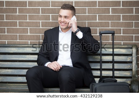 Portrait of confident young business man travelling with suitcase and waiting for transport. Successful attractive cheerful man looking sideways while talking on smartphone - stock photo