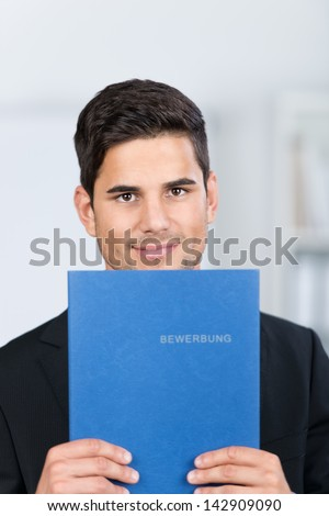 Portrait of confident young businessman holding application file in office