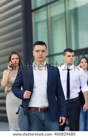 Portrait of confident young businessman in front of the group of busy business people on the move - stock photo