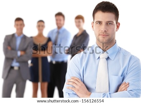 Portrait of confident young businessman standing arms crossed, team behind.