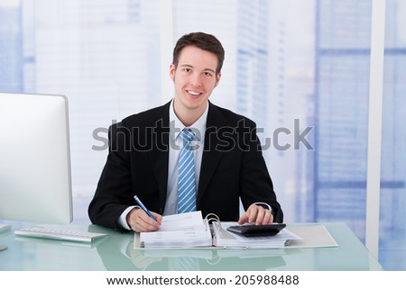 Portrait of confident young businessman using calculator at office desk - stock photo
