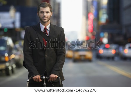 Portrait of confident young businessman with bicycle on urban street - stock photo