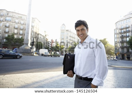 Portrait of confident young businessman with briefcase standing on city street - stock photo