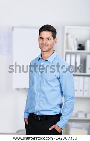 Portrait of confident young businessman with hands in pockets standing in office - stock photo