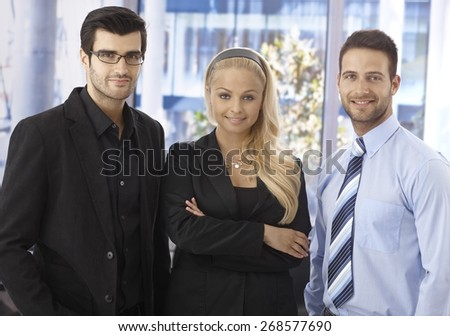 Portrait of confident young businesspeople smiling, looking at camera.