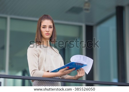 Portrait of confident young businesswoman analyzing paperwork in front of her office and looking at camera - stock photo