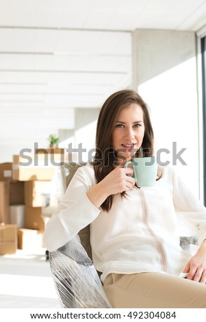 Portrait of confident young businesswoman drinking coffee in new office
