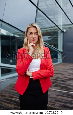Portrait of confident young businesswoman in suit reflectively looking to the camera, executive woman carefully listen to the employee, confident business woman in red jacket standing near office  - stock photo