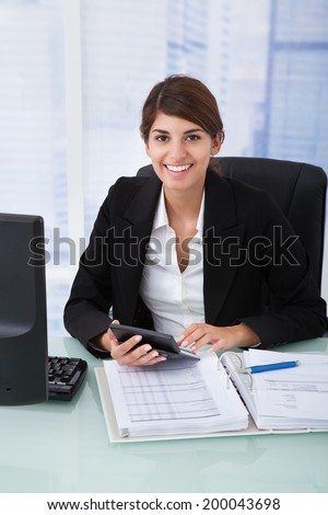 Portrait of confident young businesswoman using calculator at office desk - stock photo
