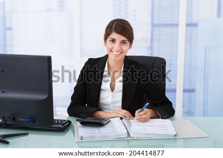 Portrait of confident young businesswoman using calculator at office desk
