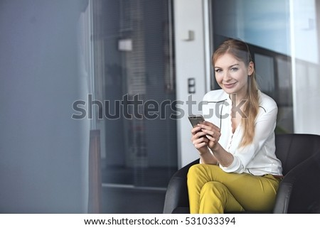 Portrait of confident young businesswoman using mobile phone on chair in office