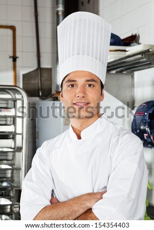 Portrait of confident young chef with arms crossed in commercial kitchen