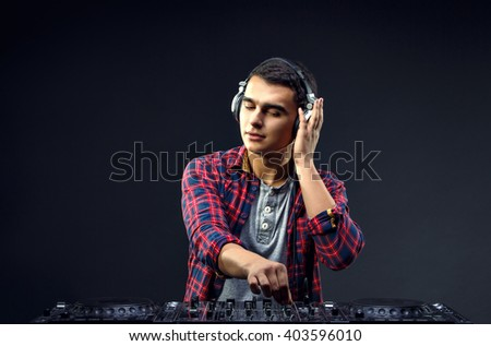 Portrait of confident young DJ with stylish haircut and headphones on head mixing music on mixer on dark background.