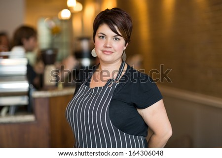 Portrait of confident young female owner smiling at cafeteria - stock photo