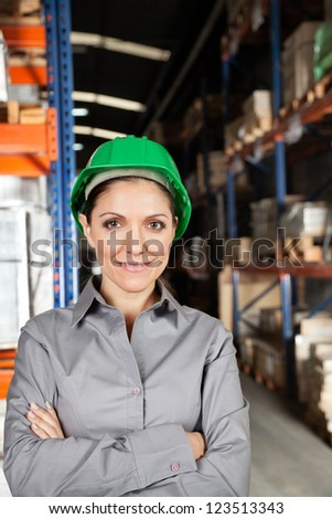 Portrait of confident young female supervisor with arms crossed at warehouse